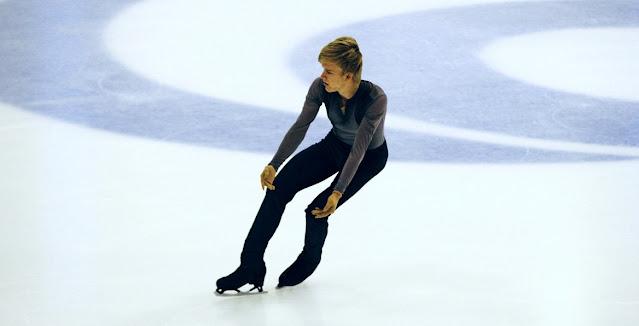 Daniel Grassl patinando no gelo. Ele é um homem loiro, usando calça preta e camisa azul de manga longa