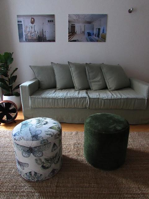 Sofá, pufs e quadros na parede