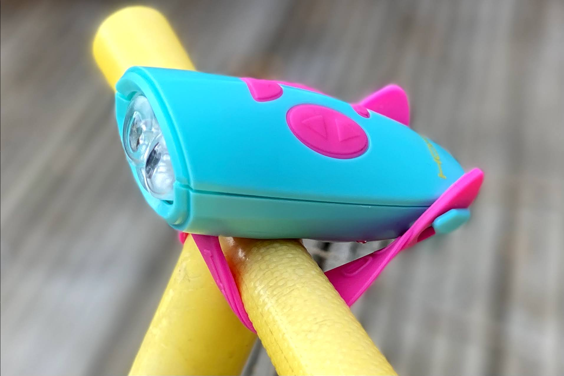 a pink and turquoise hornit mini light and noise maker on the handle bars of a yellow bumblebee scuttlebug