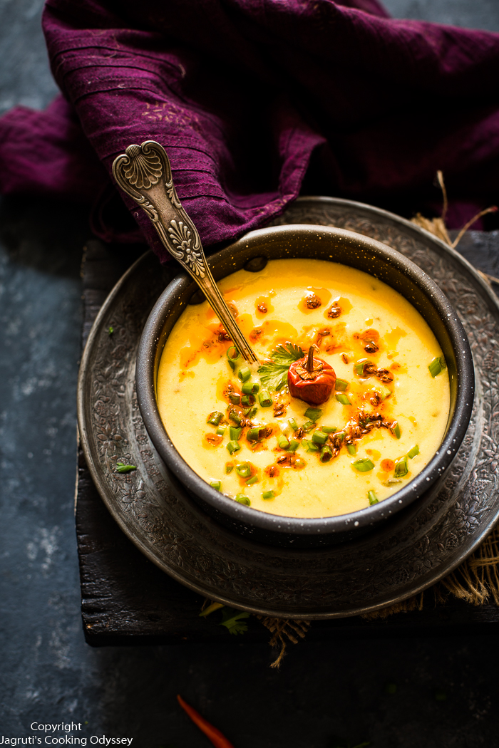 This thick and yellow Spring onion and yogurt soup is served in a pan, and garnished with spring onion.