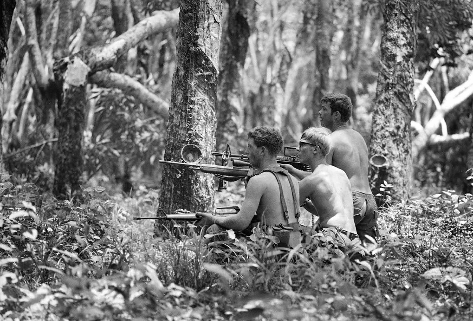Three shirtless U.S. soldiers advance through the Mimot rubber plantation in the Fishhook region of Cambodia, on May 4, 1970, taking aim at a fleeing suspect. The rubber plantation, one of the largest in Indochina, had been in operation until just a few days earlier.