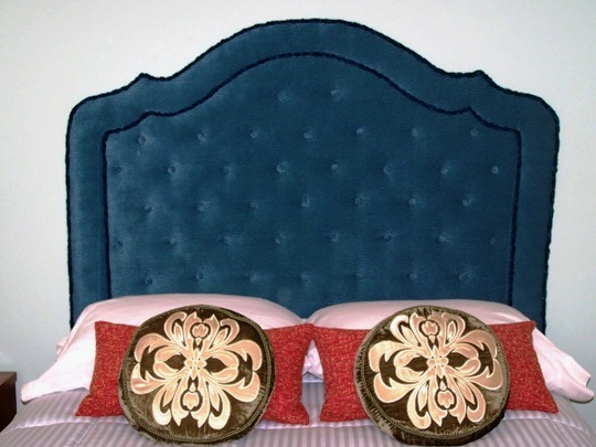 This navy blue tufted headboard looks great with the pink sheets.