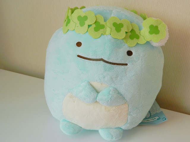 A photo of a blue dinosaur plush. His name is Tokage and he is from the Japanese San-X franchise Sumikko Gurashi. He is wearing a clover-leaf crown.