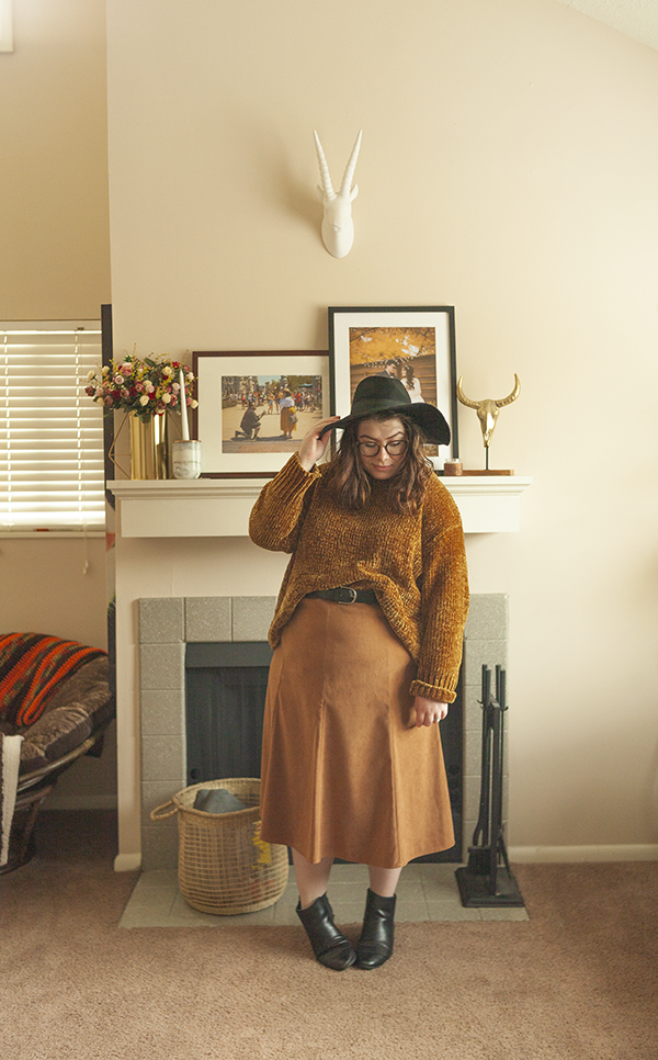 An outfit consisting of black floppy hat, dark yellow chenille sweater tucked into a brown a-line maxi skirt and black Chelsea boots.