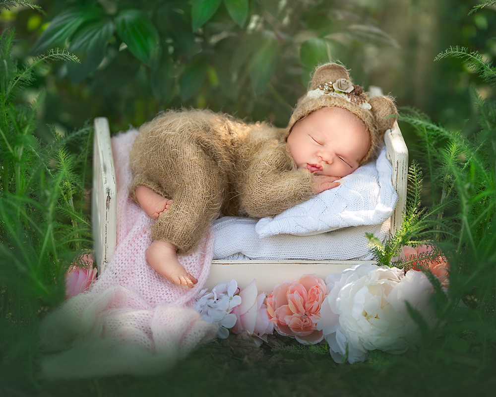 outdoor newborn bear suit baby girl with pink on a tiny bed