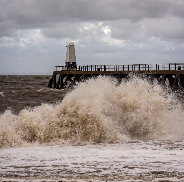 Photo of big waves crashing on the shore at Maryport in Cumbria