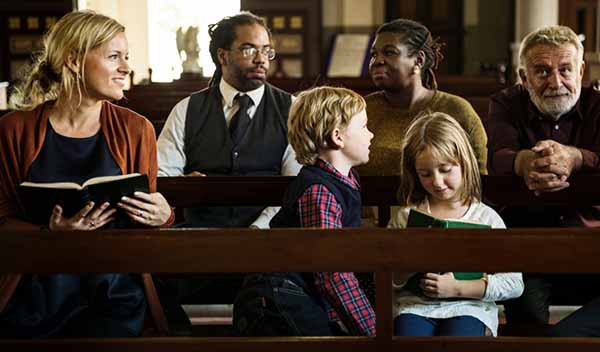 Black and white people sitting in a church with kids among them holding their bible.