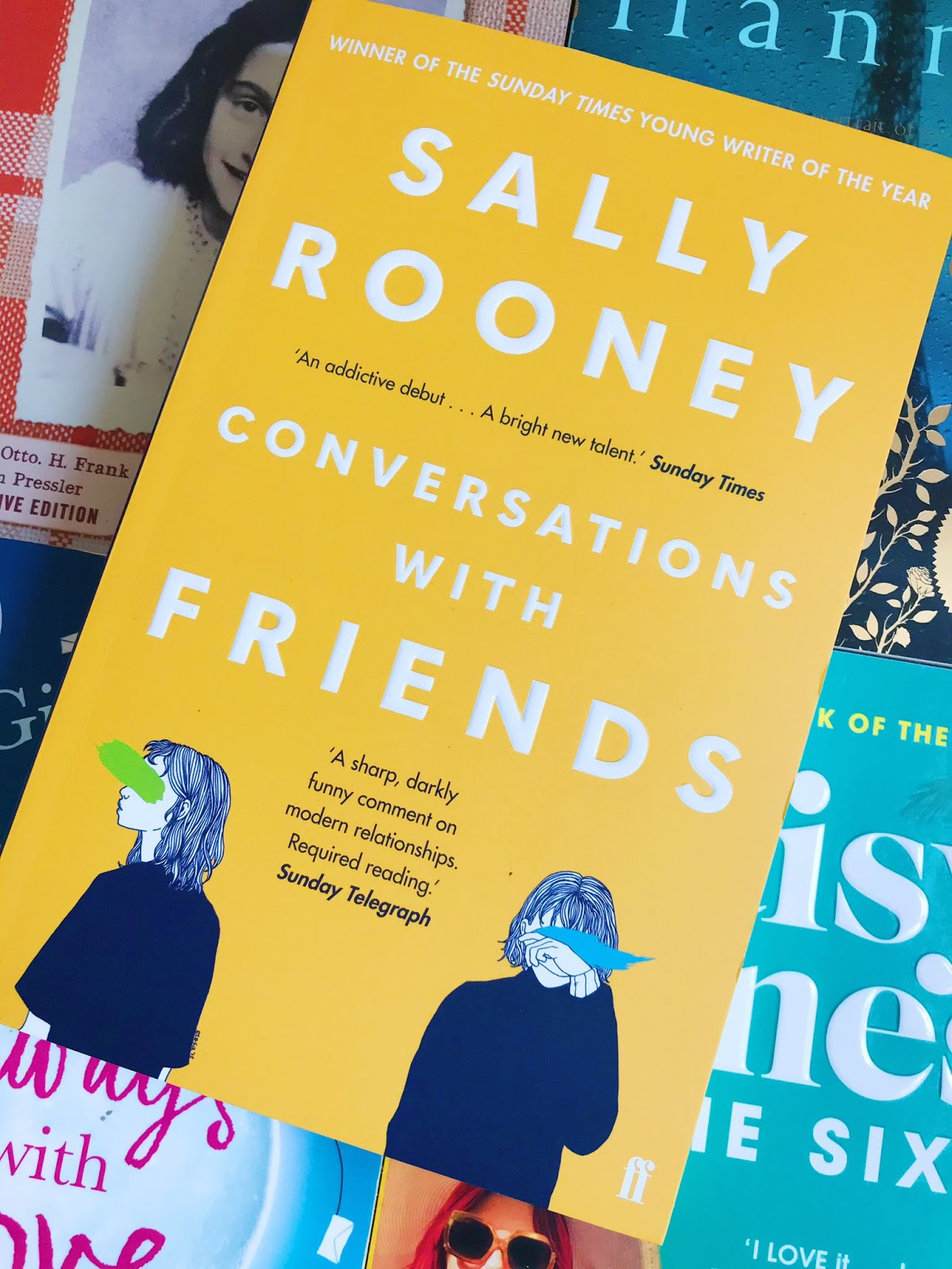 Conversations With Friends by Sally Rooney book on top of 4 other books