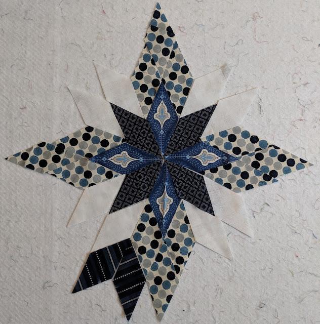 The center star has four fussy cut diamonds with fleur de lis prints alternating with a geometric navy print.