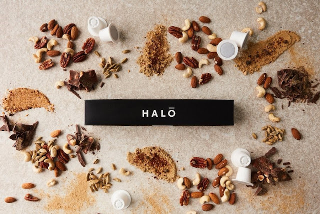 The image shows a black box of halo coffee pods surrounded by the ingredients inside of it. There are a collection of nuts and chocolate surrounding the box.