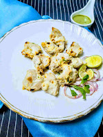 Serving Chicken malai tikka in a plate with onion and lemon wedges,green chutney in background