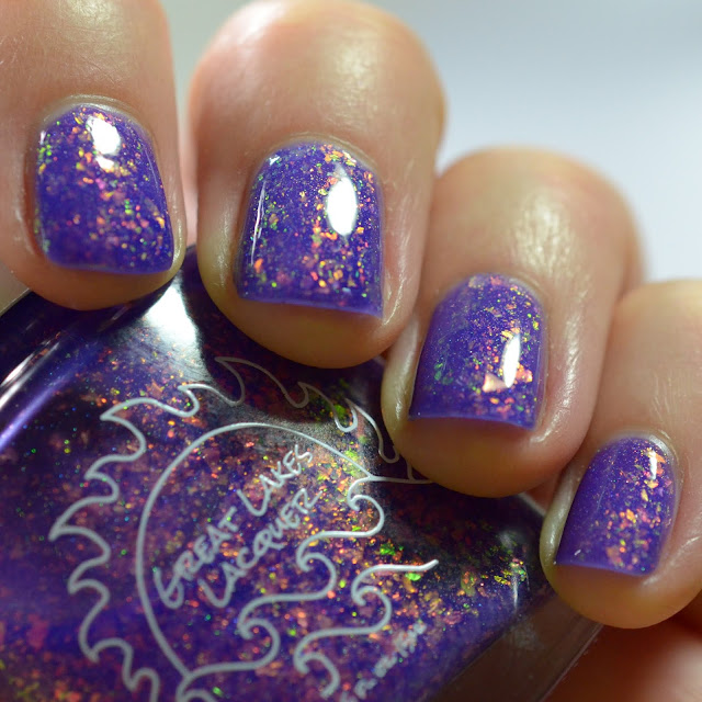 purple nail polish packed with shifty flakes that appear green and orange and gold