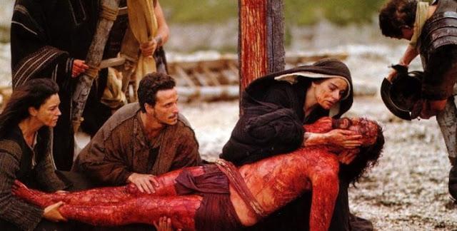Cena do filme A Paixão de Cristo: Jesus Cristo ensanguentado após o tirarem da Cruz, sua mãe e os discípulos o seguram nos braços.