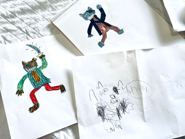 3 pieces of white paper with 3 different cartoon pirate wolves drawn on them