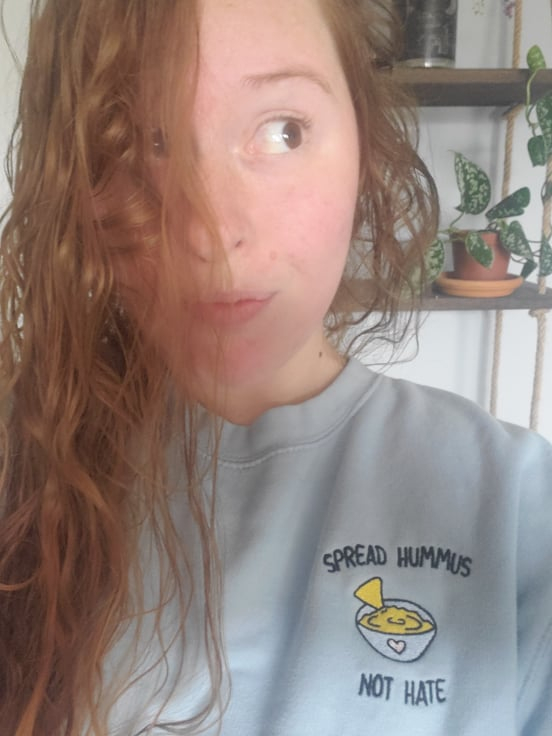Spread Hummus Not Hate embroidered pale blue crew neck jumper worn by red haired woman