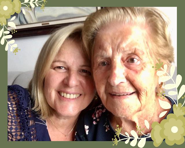 Mulher loira, cabelos lisos na altura dos ombros, com cabeça encostada em mulher idosa, com cabelos curtos e loiros. As duas estão sorrindo.