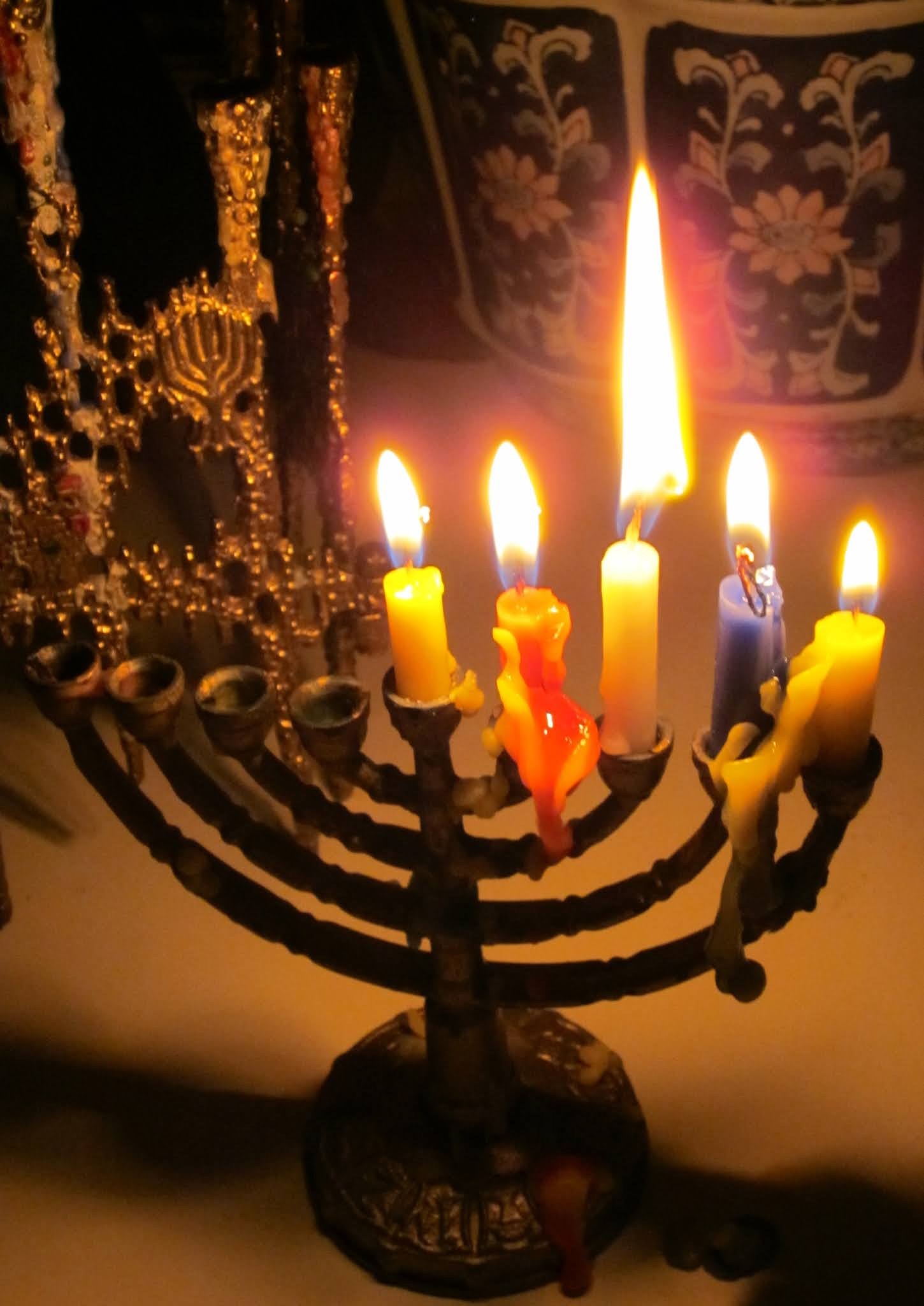 photo of a small traditional Chanukah menorah with shamash, first, second, third, and fourth candles lit