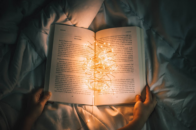 A person reading a novel kept on a quilt with a bunch of yellow fairy lights tangled around on it