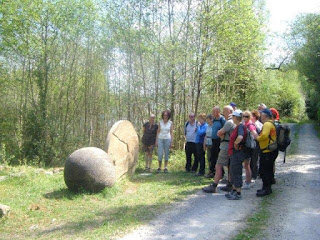 Walkers looking at one of the sculptures in a forest area Leitrim