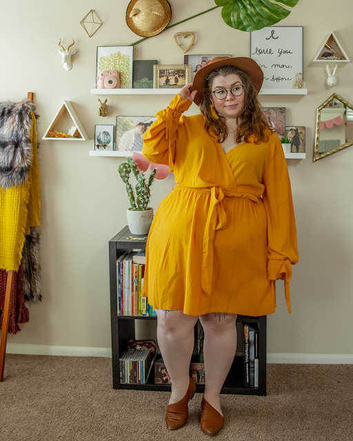An outfit consisting of a brown panama hat, yellow tassel earrings, yellow long sleeve midi wrap dress, and brown d'orsay flats.
