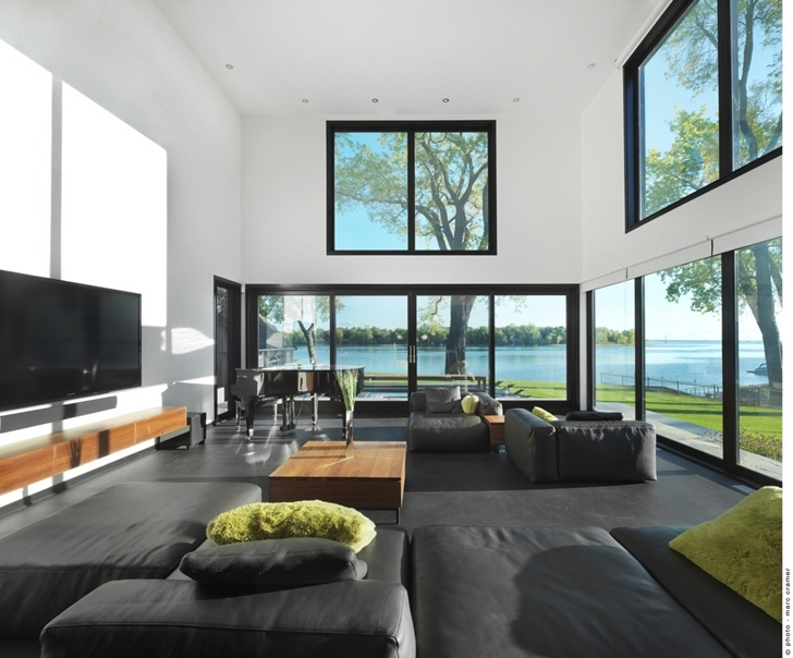 Modern living room in Renovated Bord-du-Lac House by Henri Cleinge