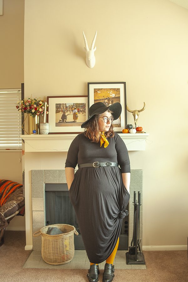 An outfit consisting of a wide brim floppy fedora, 3/4 sleeve black maxi dress, knotted at the bottom, mustard yellow tights and black boots.