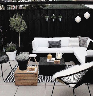 A black and white patio with tile floors, geometric print rug and egg chairs