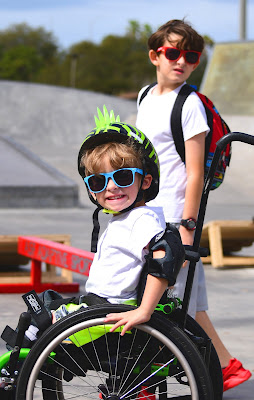 A child, wearing a bright green and black helmet and blue sunglasses, is propelling his a bright green, manual wheelchair. His helmet has a plastic, green mohawk sticking out of the top. Next to him, a boy in a white shirt and red sunglasses, turns his head to look at the camera.