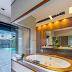 Banheiro com banheira cinza e amadeirado aberto para área externa/piscina!