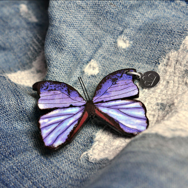 purple paper butterfly brooch on distressed denim