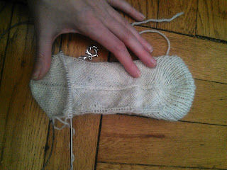 A knit sock laying flat.  Someone's hand is holding the beginning of the heel flap flat against the wooden background.  A dolphin stitch marker is locked in the work on one side.