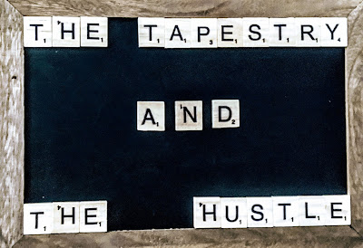 "A chalk board with Scrabble tiles on it that say ""The Tapestry and the Hustle"""