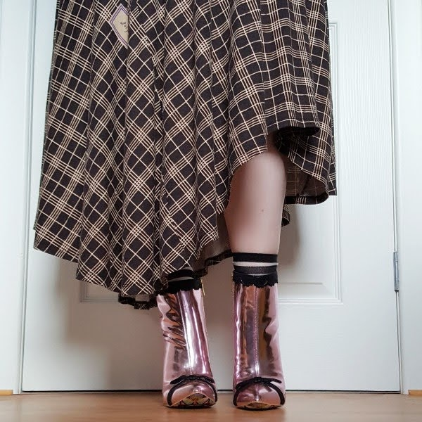 front view wearing asymmetric dress and pink mirror metallic ankle boots