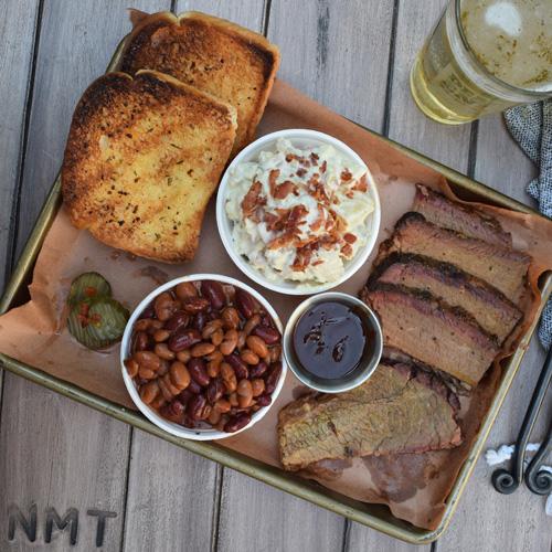 Smoked brisket platter with mixed chili beans, roasted jalapeno potato salad, and Texas toast.
