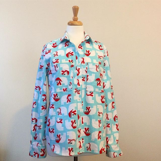 Collared button-up shirt in aqua flannel printed with cartoonish polar bears wearing Santa hats and scarves