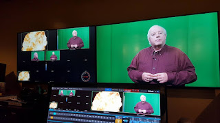 William Elliott seen on control room monitors during the recording of his latest program, remember, remember. He is wearing a burgundy colored shirt and stands in front of a green curtain which will be taken out of the shot later as graphics are incorporated into the program.