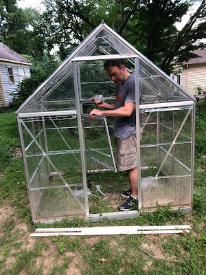 Alex standing in a small greenhouse looking at the pieces he's holding. He's sweaty. And kinda mad