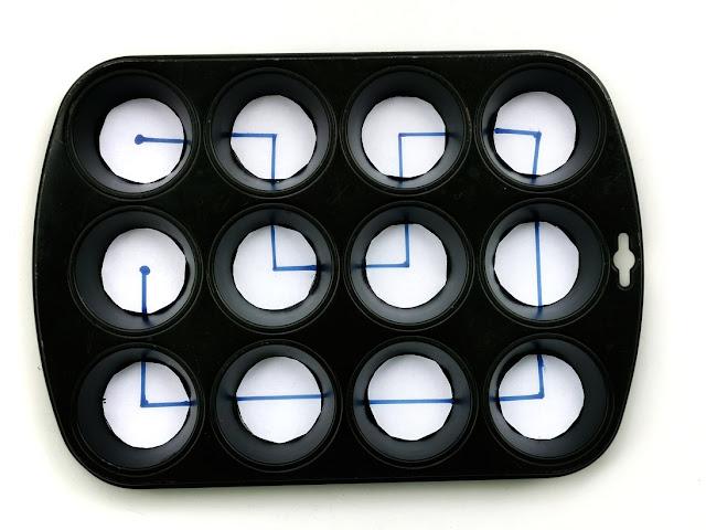 na zdjęciu czarna tacka do pieczenia 12 babeczek a w każdym wgłębieniu kółko wycięte z papieru z narysowanym różnym układem linii