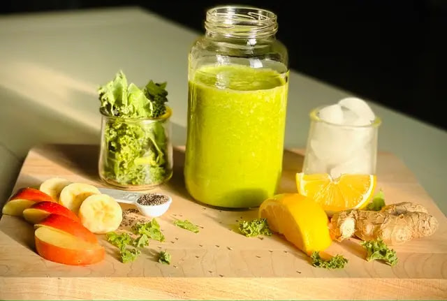 Manzana, plátano, naranja, jengibre y especias rodeando un vaso de cristal con licuado verde sobre una tabla de madera