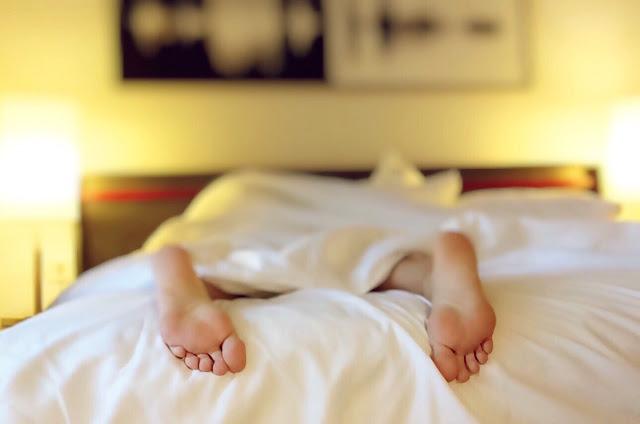 """persona tumbada en la cama durmiendo """"a pierna suelta"""""""