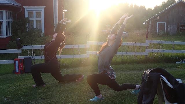 Kaksi henkilöä tekee joogaliikkeitä nurmikolla auringon noustessa.