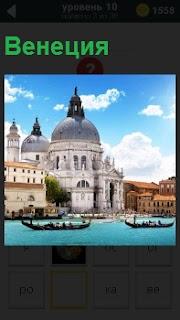 Город на воде и гондолы с пассажирами направляются к причалам Венеции, на которых уже стоят новые туристы