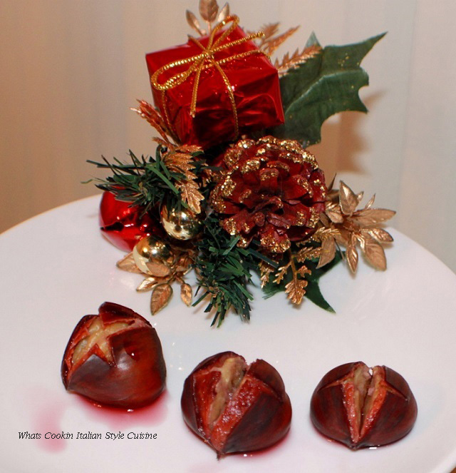 these are chestnuts on a white plate with a holy ornament for Christmas in the background