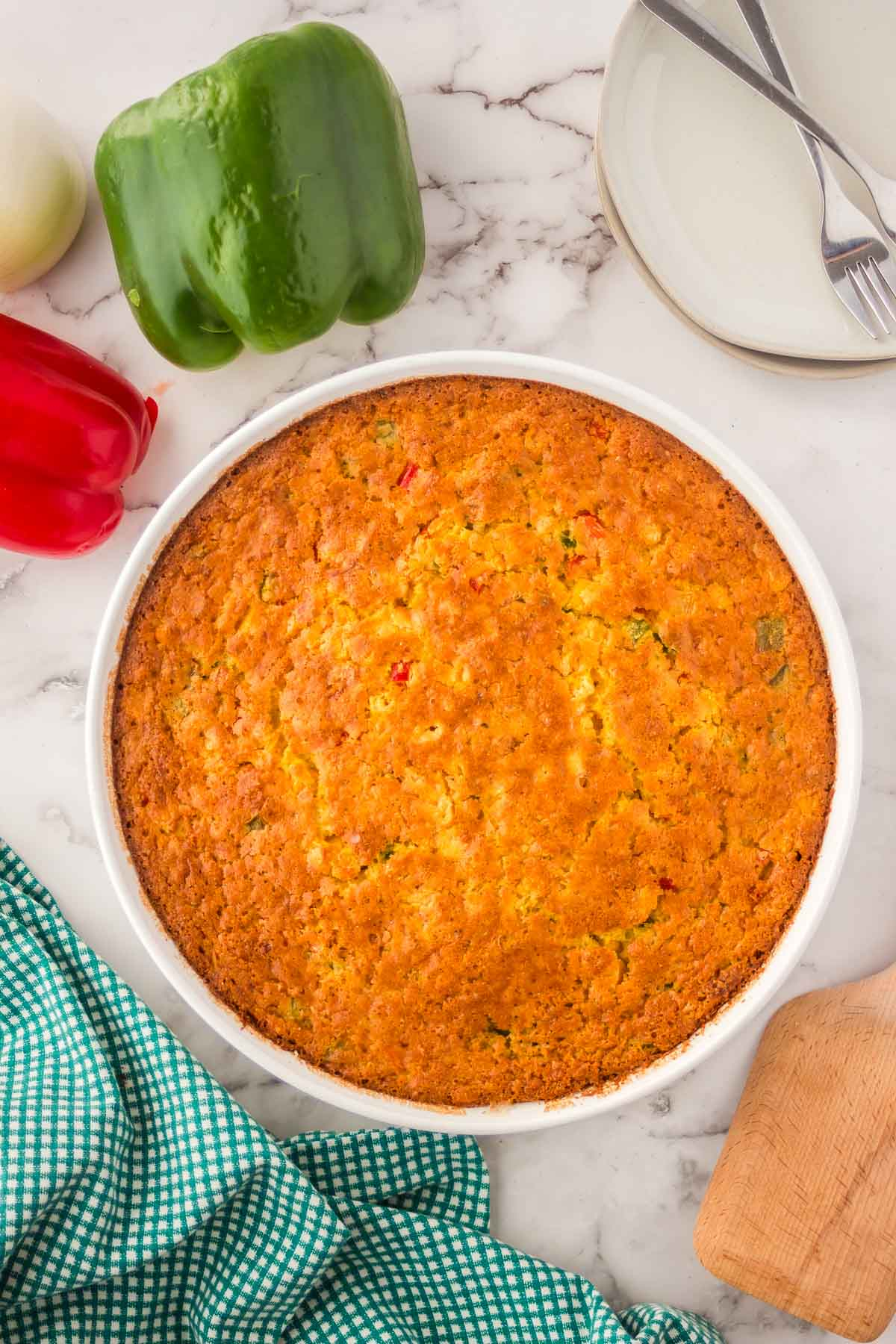 Baked trini corn casserole, in a circular white dish with a green bell peppers, plates and napkin