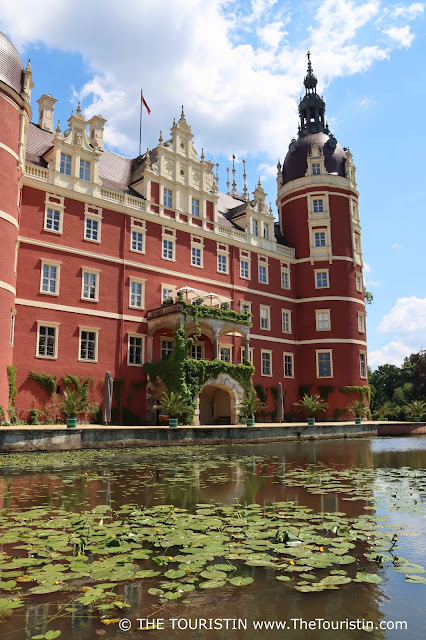 Water lilies on a lake in front of a red-ish coloured renaissance castle with an overgrown balcony under a blue sky