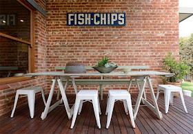 mesa rústica de madeira com pés de cavalete usada na área externa