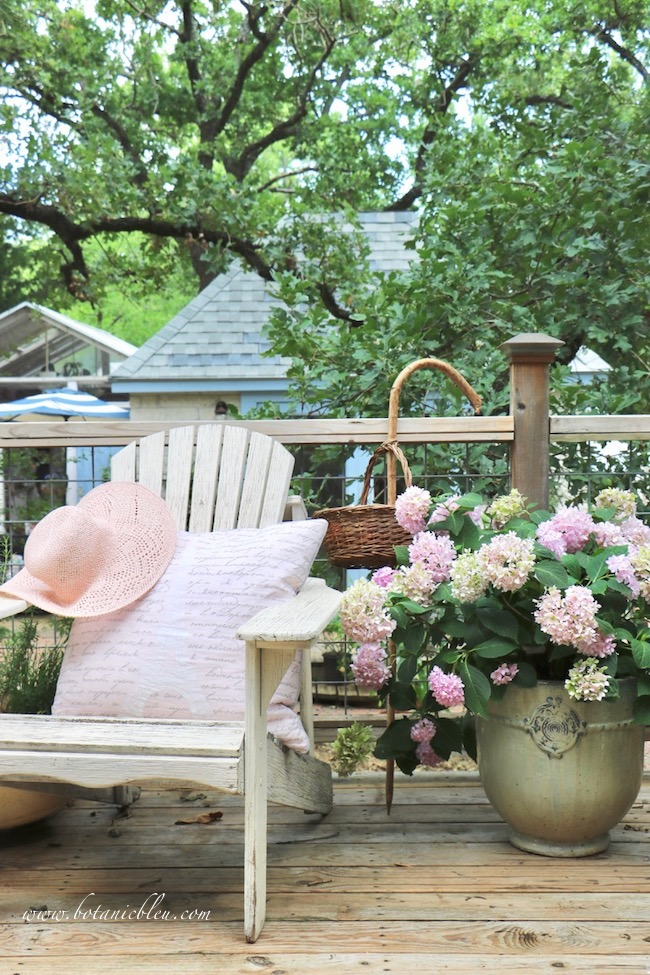 Peach colored straw hat and French script pillow on adirondack chair with pink hydrangeas