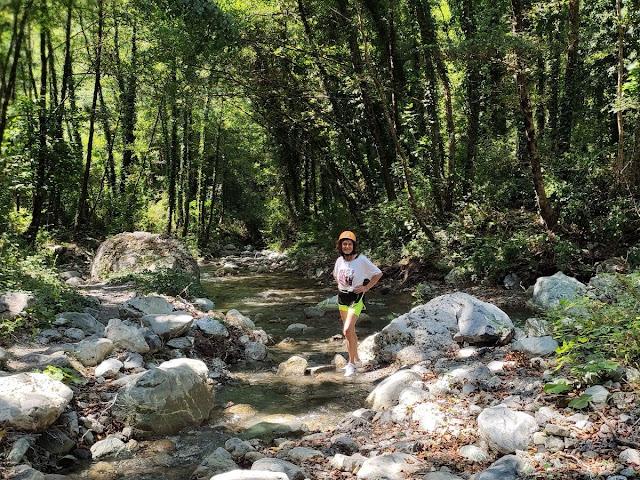 Donna nella natura vicino ad un torrente con alberi