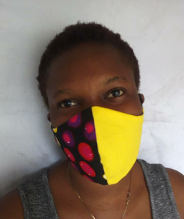A lady wearing a bright coloured and patterned Ankara Facemask