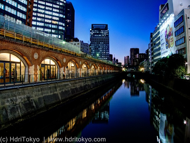 a train viaduct along Kanda-river at night. reflections of buildings and the viaduct on the water